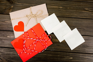 white leaflets and red envelope lying on wooden surface