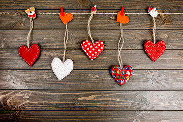 Red cloth hearts hang on the rope on wooden background