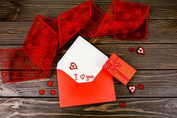 Red envelope with card 'I love you' inside lies among red decora