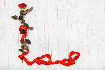 Red rose with long red silk ribbon lies on white wooden floor