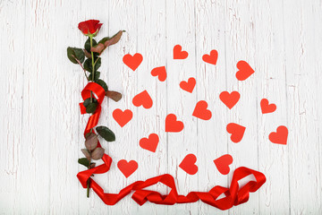 Red rose with long red silk ribbon surrounded with paper hearts