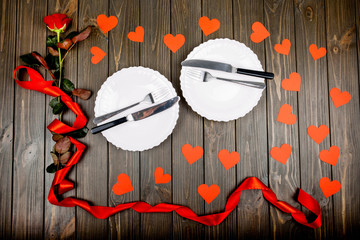 plates with cutlery and a red rose with a ribbon lie on wooden s