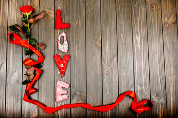 Red cloth letters LOVE and rose with long ribbon lie on wooden f