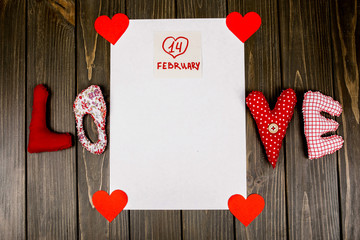 Cloth letters LOVE lie over empty white card with lettering '14