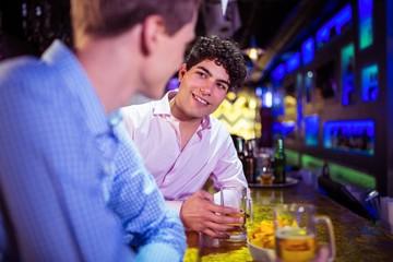 Friends talking at bar counter