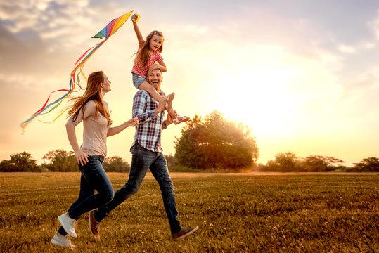 familie mit tochter rennt und lässt drachen steigen