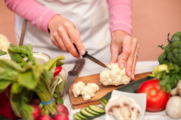 Woman slicing and preparing cauliflower