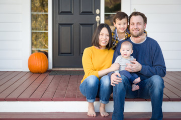 Young Mixed Race Chinese and Caucasian Family Portrait On Their Front Porch.