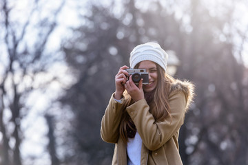 Portrait of winter girl taking photo with vintage camera