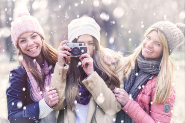 Group of young college girls  with vintage camera on snowy day