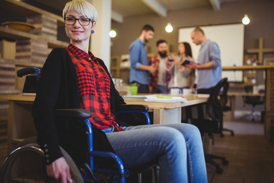 Confident woman on wheelchair while colleagues in background