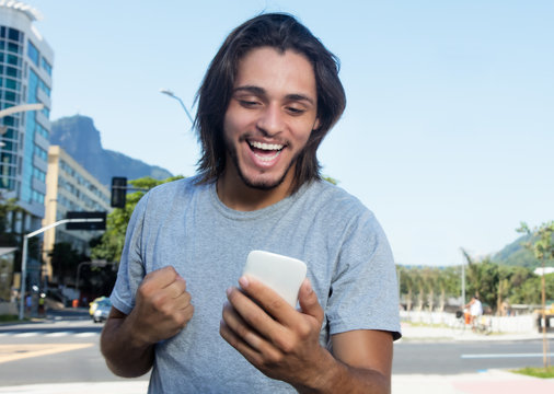 Hipster with long brunette hair receiving good news on phone