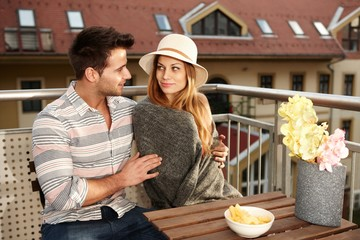Young couple sitting on terrace smiling