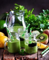 Green smoothies from fresh kiwi, avocado, apple, lemon, baby spinach and parsley. Healthy eating.