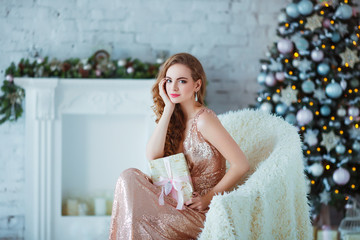 Holidays, celebration and people concept - young woman in elegant dress over christmas interior background. Image with grain