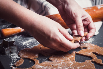 Cooking Christmas gingerbread cookies on a dark background