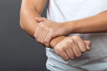 Close up, man hand holding his wrist on gray background