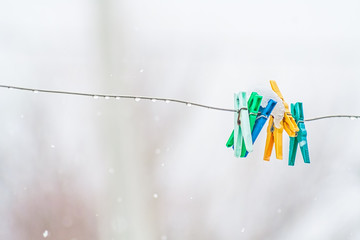 Clothespins on the aluminum wire in the wet snow, close-up
