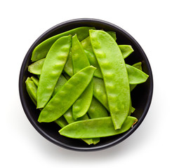 Bowl of snow peas isolated on white from above