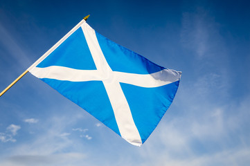 Scottish flag, also known as St Andrew's Cross, flying in bright blue sky