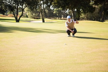 Distant view of golfer crouching and looking his ball