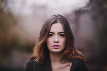 Attractive, charming young woman in a white cotton dress and dark coat walking in the autumn Park. Cloudy. Soft colors of nature. The melancholy mood. Wall mural