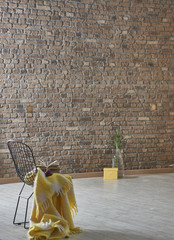 brick wall decoration with black chair and yellow wrap