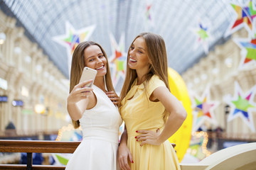Two smiling women take a picture of herself with a smart phone