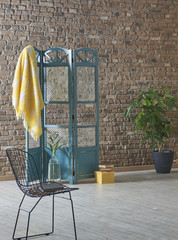 dressing area with yellow wrap concept in front of the brick wall and flowers