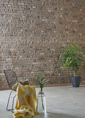 decorative black chair in front of the brick wall with wrap and flowers