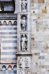 Facade of Cathedral in Como city, Lombardy, Italy. Exterior in from of the cathedral with Italian, Architectural, detail, sculpture, bas-relief Masonry carving.