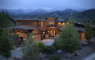 Residential home in the Utah mountains, at dusk with ski slopes in background.