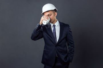 Handsome young engineer in a helmet standing on gray background with a cup of coffee drink it