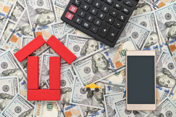 Smartphone, calculator, toy car and a house built of blocks laid out on a background of dollars, a top view
