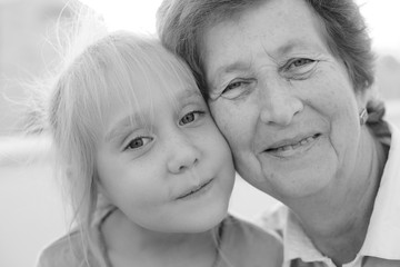 Portrait of beautiful 70 years old woman with 5 years old grandd