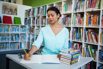 Woman writing on notebook against bookshelf in library