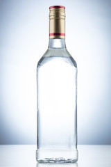 Empty tequila alcohol bottle with no label and a gold and red cap on a white background