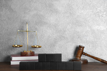 Black wooden cubes and law composition on grey background