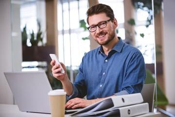 Portrait of confident executive using cellphone