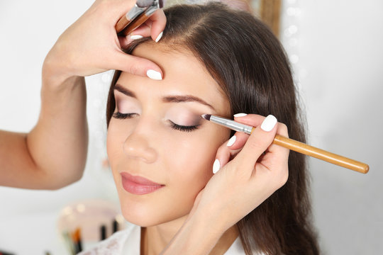 Wedding preparation. Professional makeup artist applying eye shadow to bride