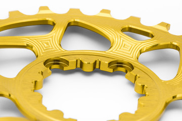 Golden oval chainring detail at white background, isolated