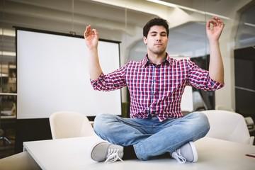 Businessman performing yoga in meeting room