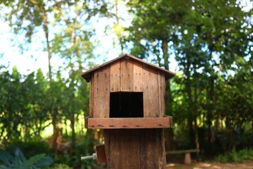 A wooden bird house with green background