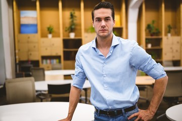 Confident businessman with hand on hip in meeting room