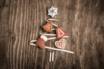 Christmas tree made of branches and gingerbread cookie as background