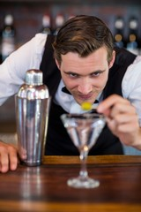 Bartender garnishing cocktail with olive