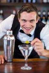 Portrait of bartender garnishing cocktail with olive