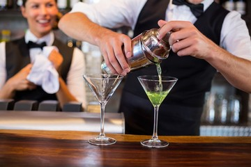 Mid section of bartender pouring cocktail into glasses