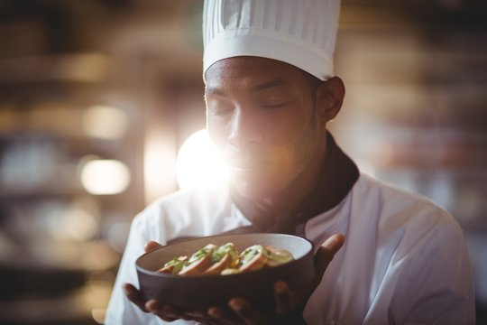 Close-up of chef with eyes closed smelling food