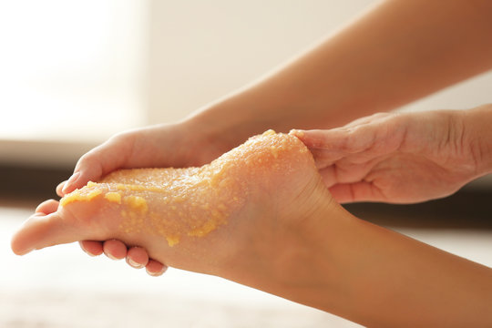 Spa concept. Hands massaging female foot with scrub